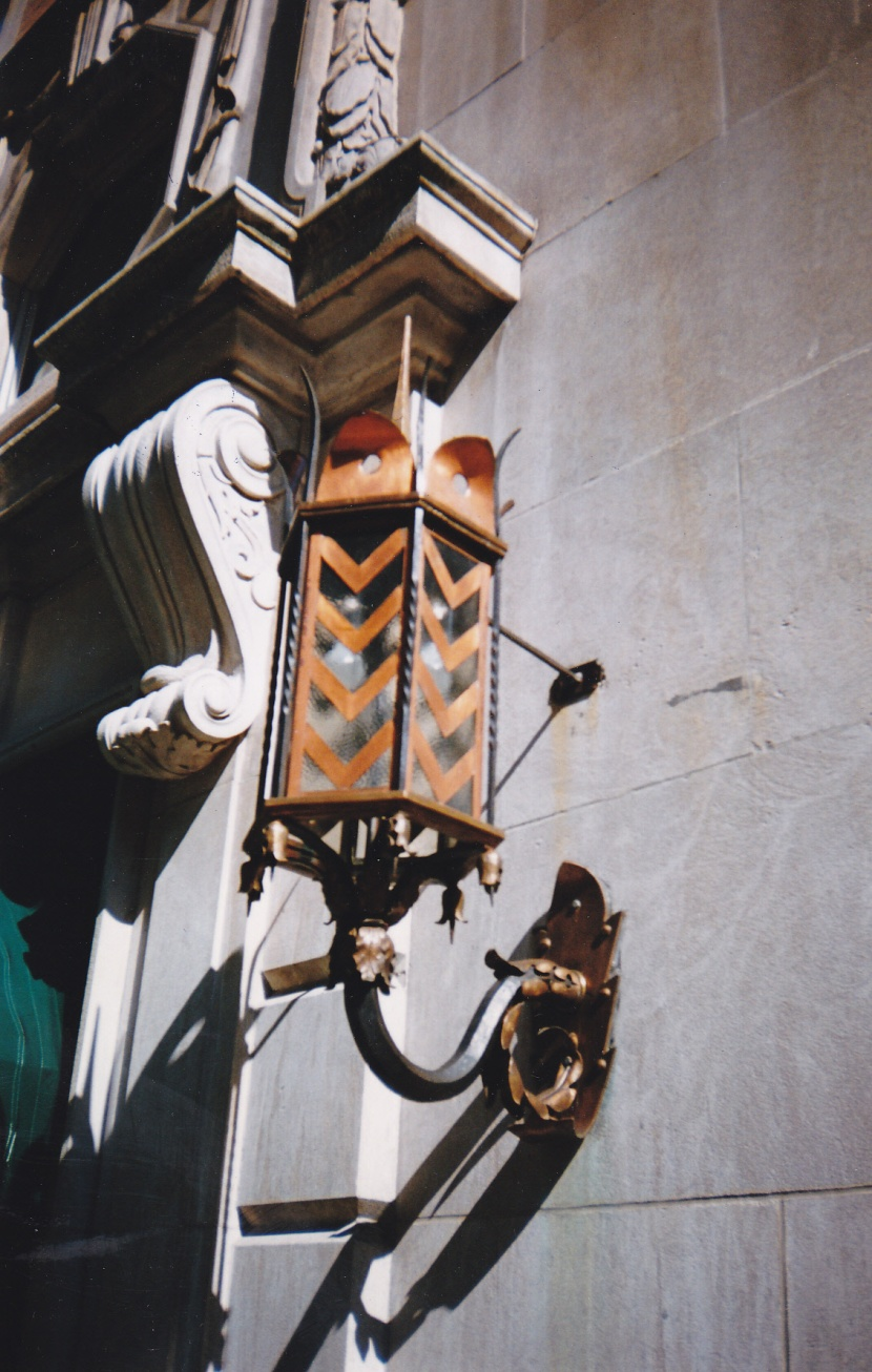 This wrought iron, copper, and bronze exterior sconce was painted black